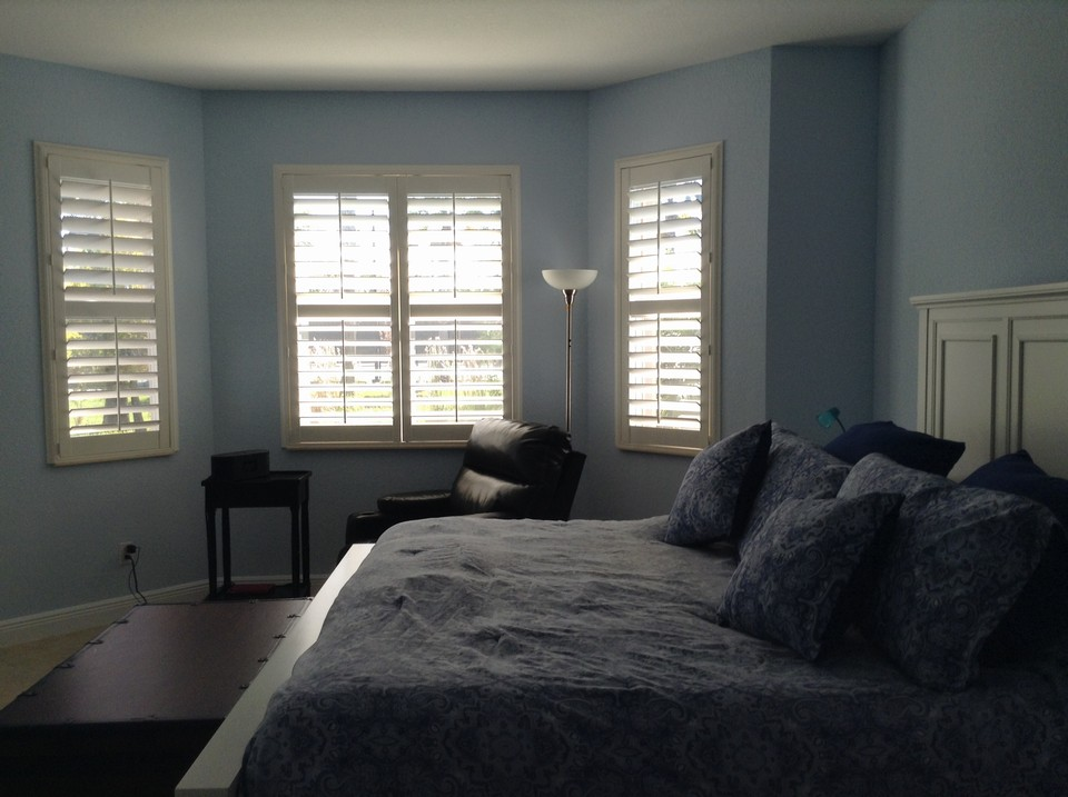 master bedroom with bay window and plantation shutters